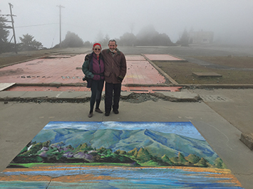 Gary Yost and Genna Panzarella stand with the chalk drawing